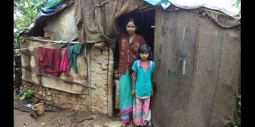 Sakshi with her mother in front of their hut