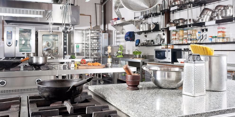 A professional kitchen with strategically placed cooking utensils and essentials.
